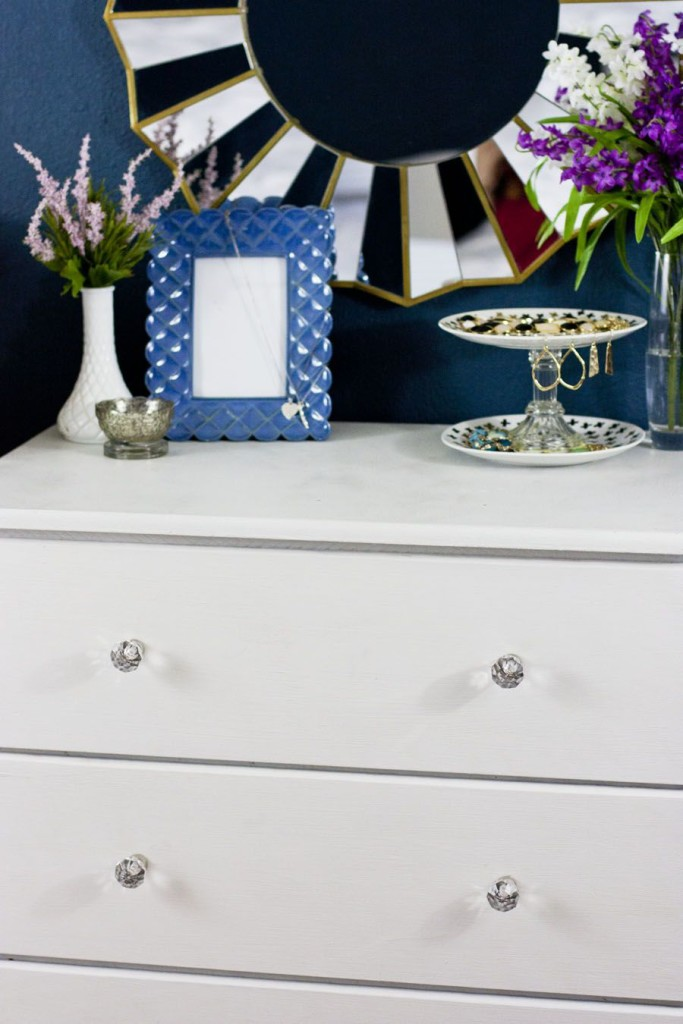 Gorgeous white chalk painted dresser and beautiful styling on top. Love that sunburst mirror and jewelry tray. Beautiful One Room Challenge bedroom makeover with navy walls.