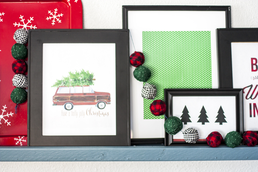 This Christmas picture ledge looks amazing! I love this above the couch as an alternative to a gallery wall. So easy to swap out the frames and art with the seasons. The holiday art looks pretty and the fabric garland is fun, too.