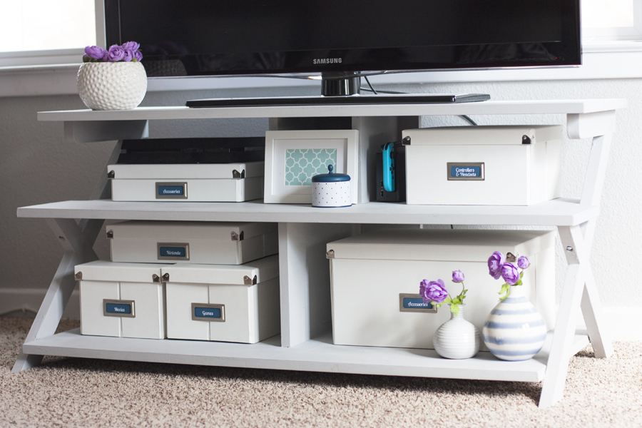 Love this organizing solution for a tv stand! Organize video games and all of the accessories inside pretty storage boxes. These Pop 'N Store boxes are so cool because they look nice and fold flat when not used. I love how this blogger added bookplate labels to them! That painted TV stand plus the storage boxes made such an improvement!