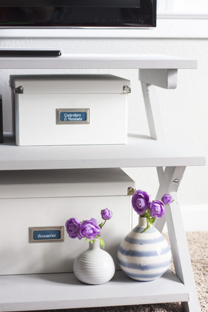 Love this organizing solution for a tv stand! Organize video games and all of the accessories inside pretty storage boxes. These Pop 'N Boxes are so cool because they look nice and fold flat when not used. I love how this blogger added bookplate labels to them! That painted TV stand plus the storage boxes made such an improvement!