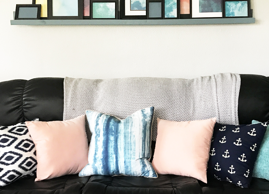 This spring living room is beautiful! Love the pink, aqua and navy throw pillows and that painted TV stand. Simple spring decor | spring family room | blue decor | living room decor