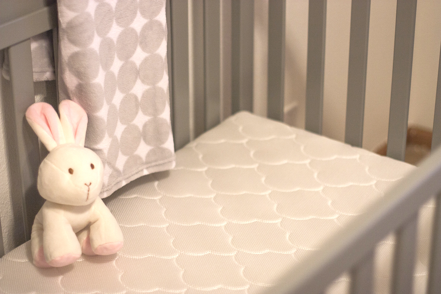 It doesn't take much to transform a room! Check out how pretty this nursery looks now that it's not hideous pastel green anymore. This white nursery is serene, calm and filled with baby necessities like the beautiful gray crib and the Newton Wovenaire crib mattress.