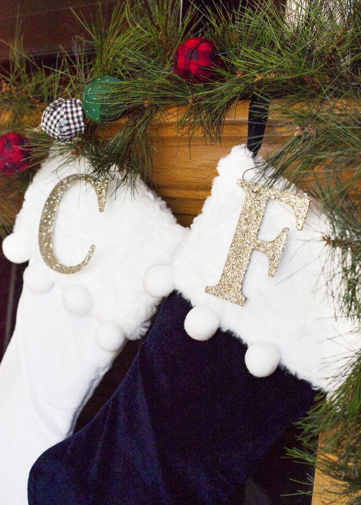 These velvet stockings with pom poms are adorable! And what a cute idea to add glitter letters to personalize Christmas stockings. christmas home tour | holiday homes | christmas house | christmas tree pictures | christmas mantel | christmas living room | christmas blog home tour christmas home tour | holiday homes | christmas house | christmas tree pictures | christmas mantel | christmas living room | christmas blog home tour