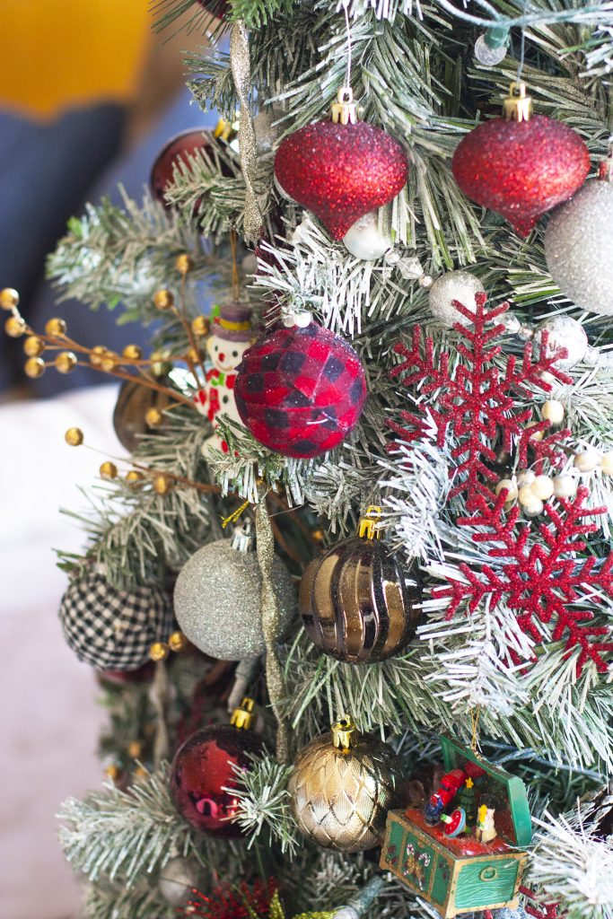 This thrifty Christmas tree is so pretty! Genius use of that spray snow you can find for cheap at Walmart. I love how she updated an old Christmas tree. christmas home tour | holiday homes | christmas house | christmas tree pictures | christmas mantel | christmas living room | christmas blog home tour