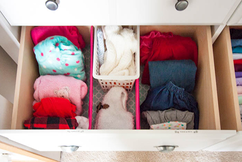 nursery dresser drawer with organized baby clothes