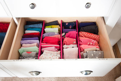organized baby clothes in white dresser