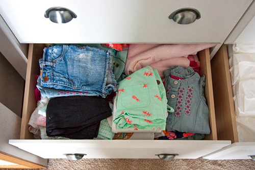 baby clothes stacked in a dresser drawer