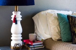 white-lamp-on-nightstand-by-bed