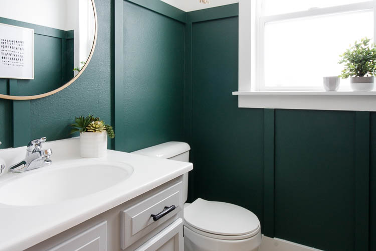 white-painted-sink-and-gray-vanity-in-green-bathroom