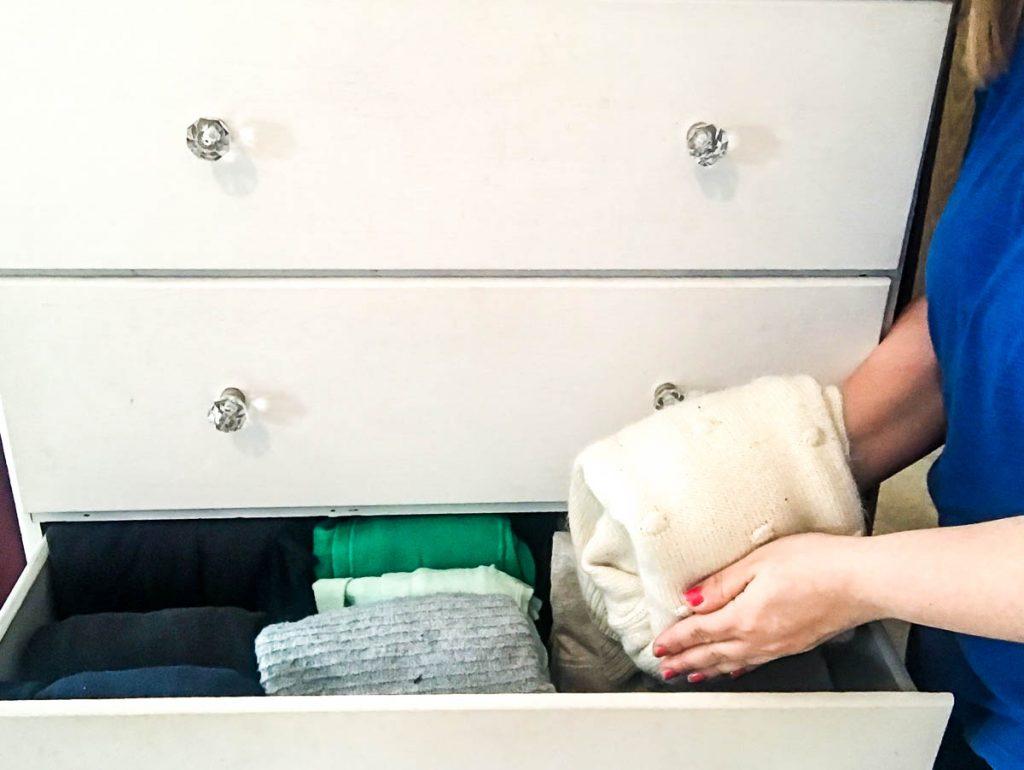 girl-folding-sweater-next-to-organized-dresser-drawer