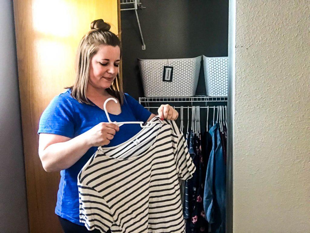 woman-hanging-striped-shirt-on-hanger
