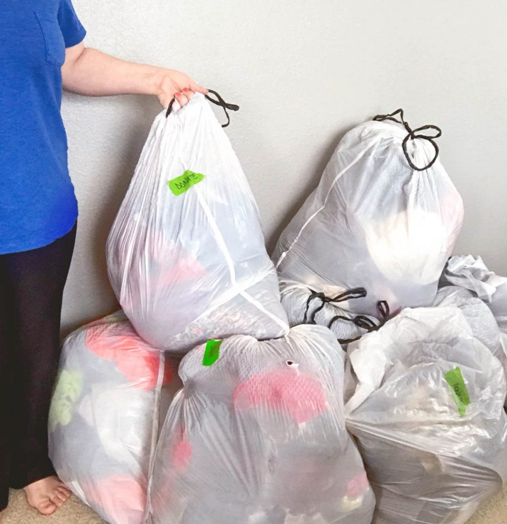 girl-standing-next-to-pile-of-8-full-trash-bags-of-clothes