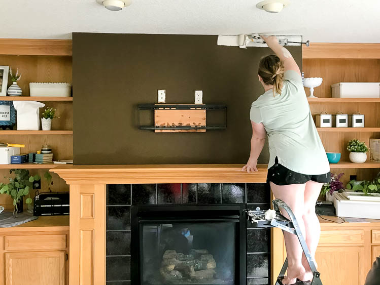 woman-painting-ege-of-wall-white-above-fireplace