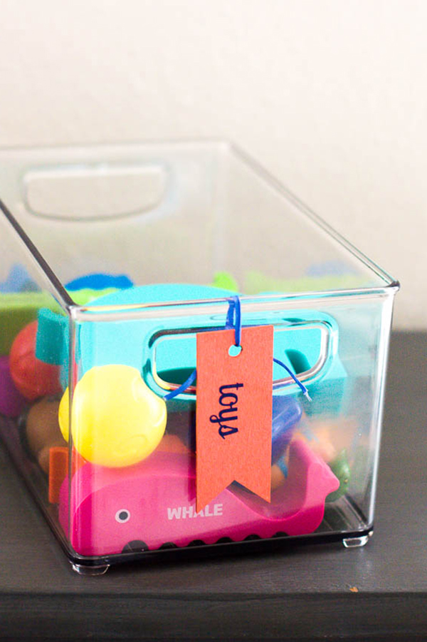 coral-wooden-label-tied-onto-clear-storage-bin-of-toys