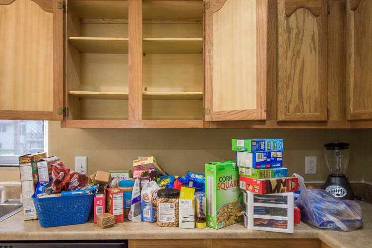 empty-upper-kitchen-cabinet-with-pantry-foods-on-counter