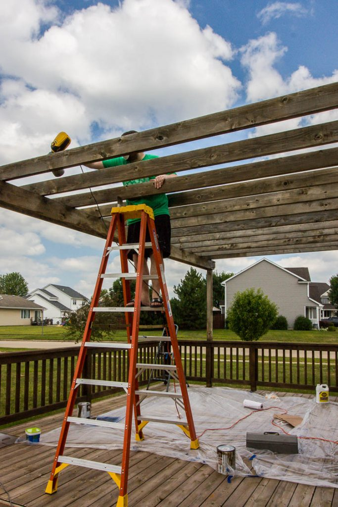 spraying-stain-on-pergola