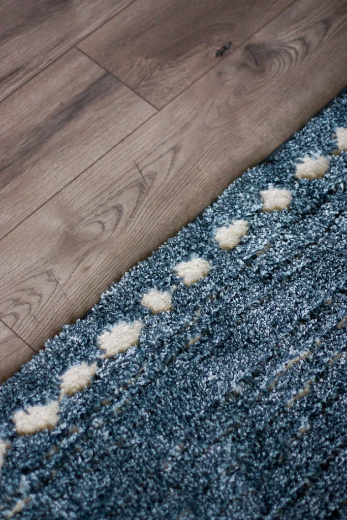 navy-blue-area-rug-and-gray-wood-floor