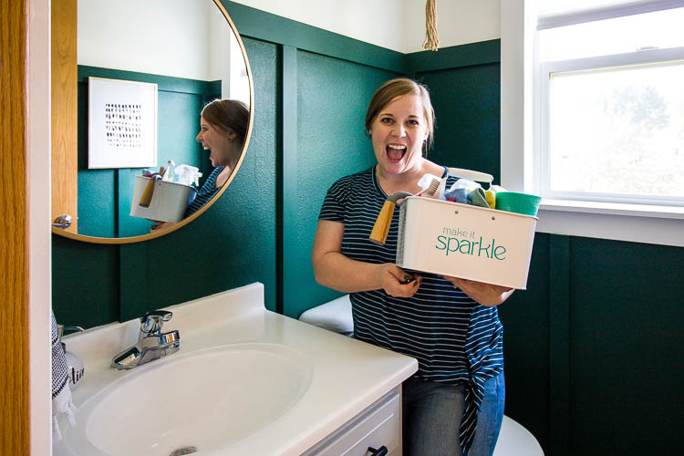 emily counts holding organized cleaning caddy in green bathroom