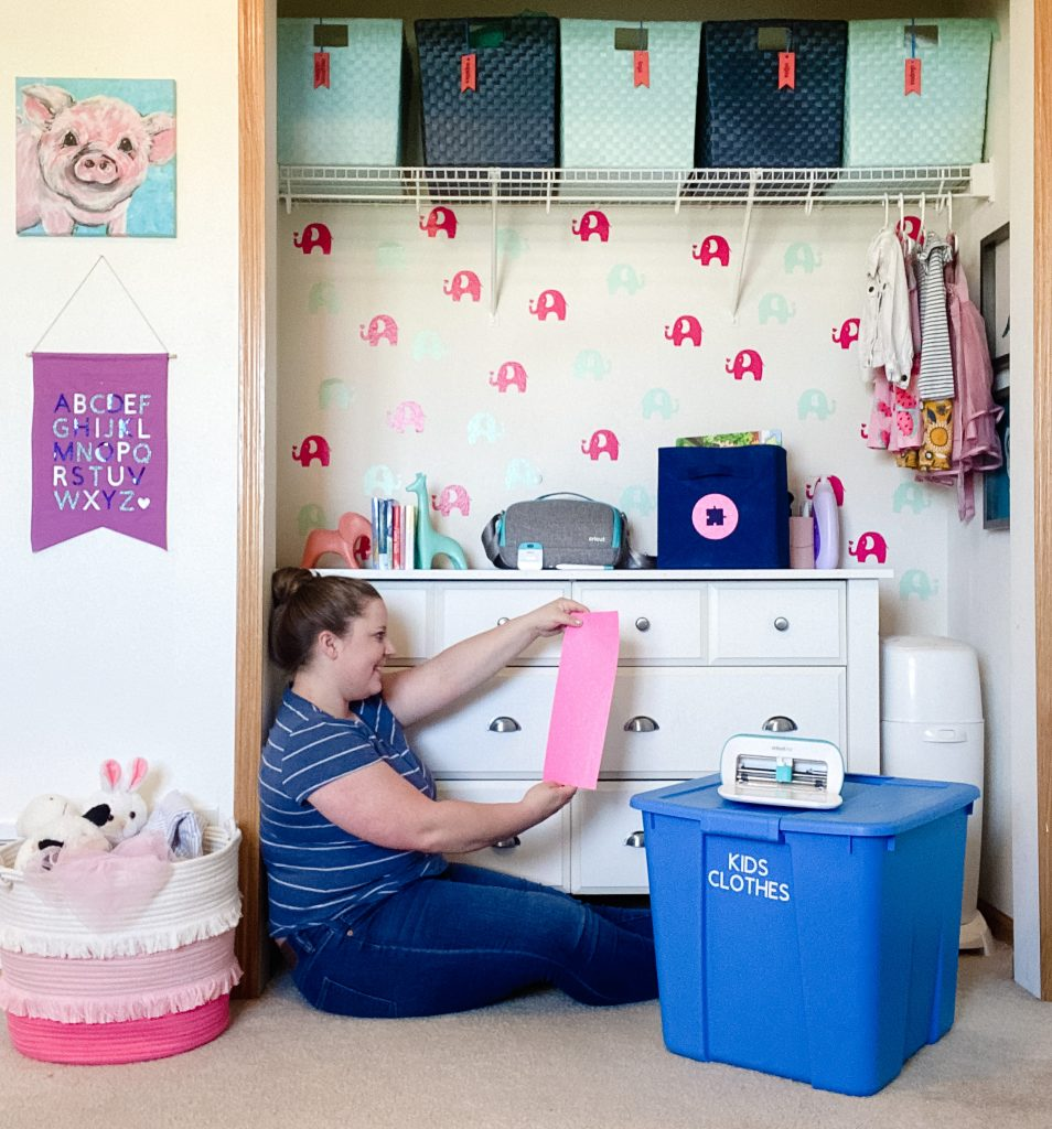 lifestyle image of emily counts sitting on floor of nursery with Cricut Joy and labeled bins