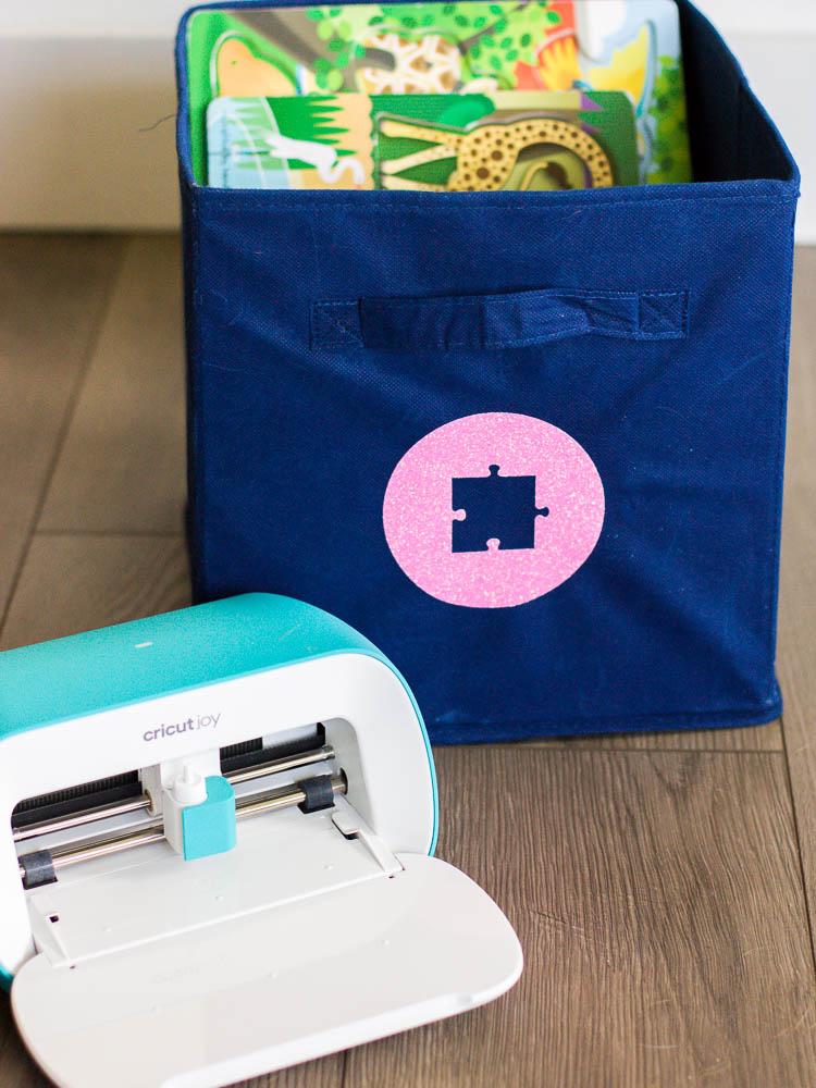 cricut joy on floor next to blue fabric bin with pink iron-on label