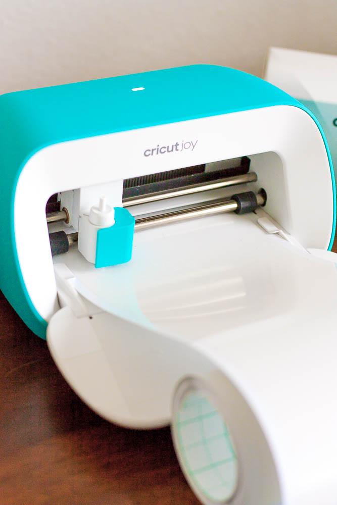 close up of Cricut Joy machine cutting white label vinyl