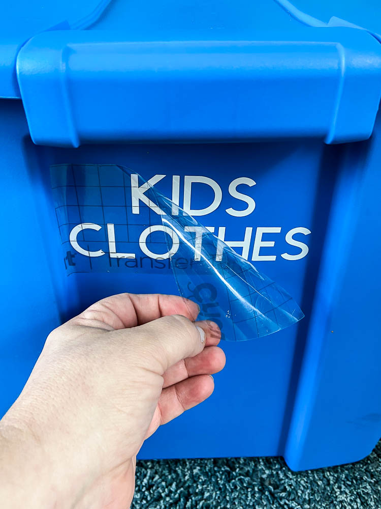 """hand pulling transfer paper off of white letters """"Kids Clothes"""" on a blue tote"""