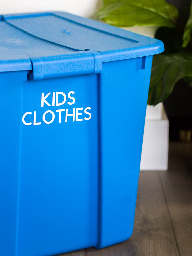 """blue plastic tote with """"kids clothes"""" label in white vinyl"""