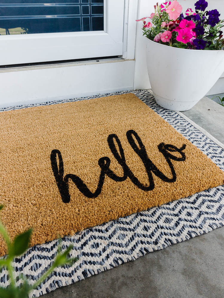 """a brown door mat with a cursive """"hello"""" painted onto the mat in black sits on the front porch in front of the door with a pot of flowers."""