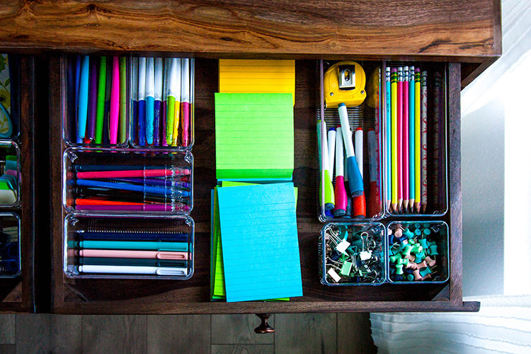 desk drawer with organizing bins full of colorful pens and office supplies