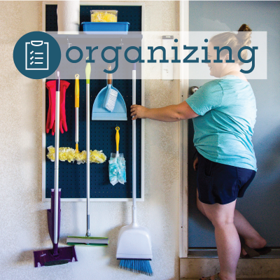 organized pegboard with brooms hanging on it