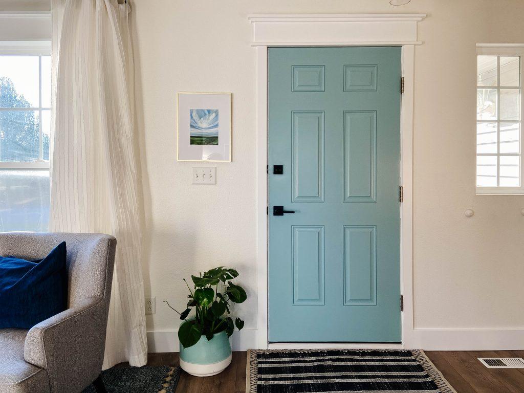 blue front door interior with dark modern hardware