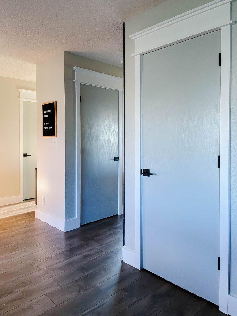 gray interior doors with white trim and dark hardware