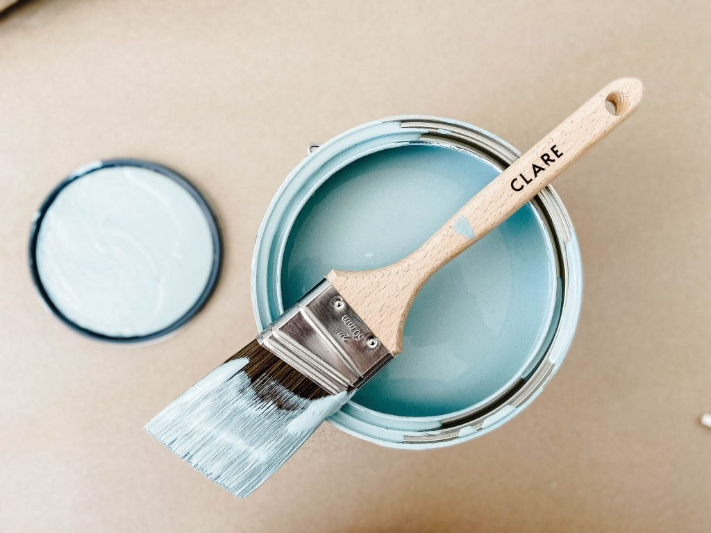 open can of blue paint with a used paintbrush