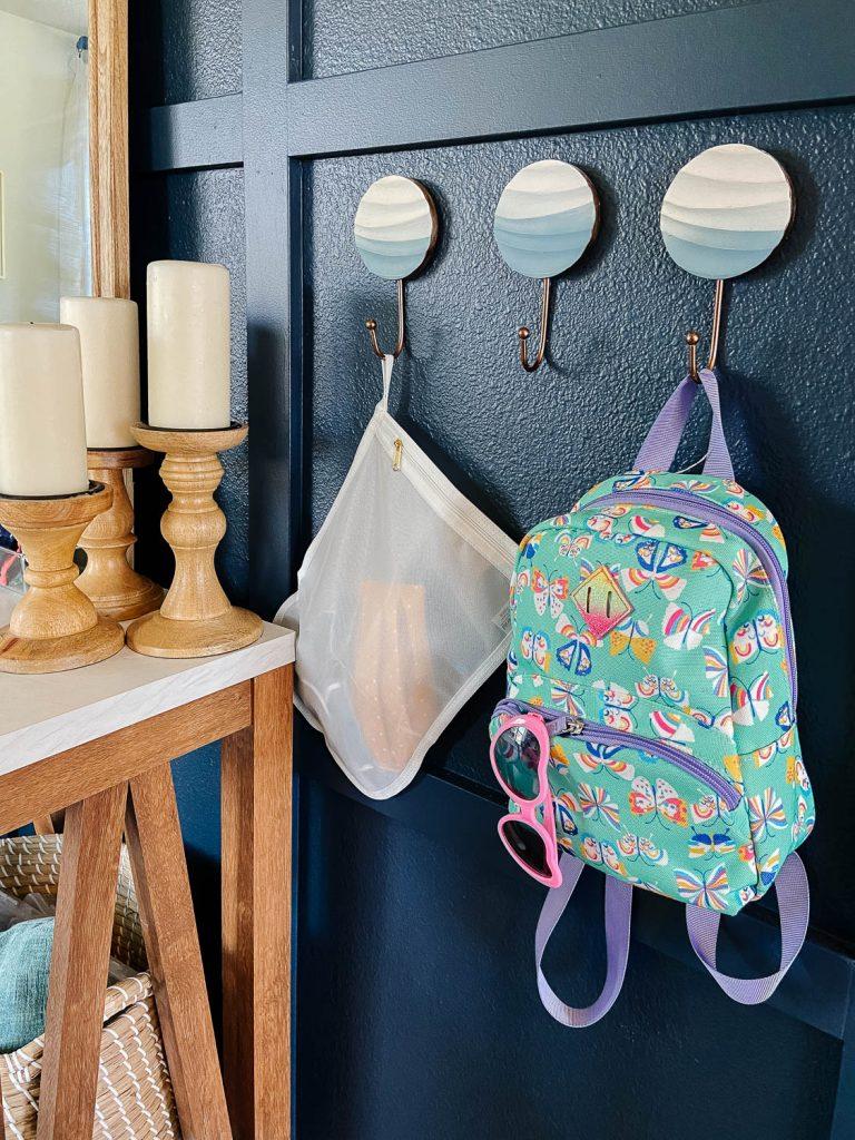 backpack and mesh laundry bag hanging on coat hooks