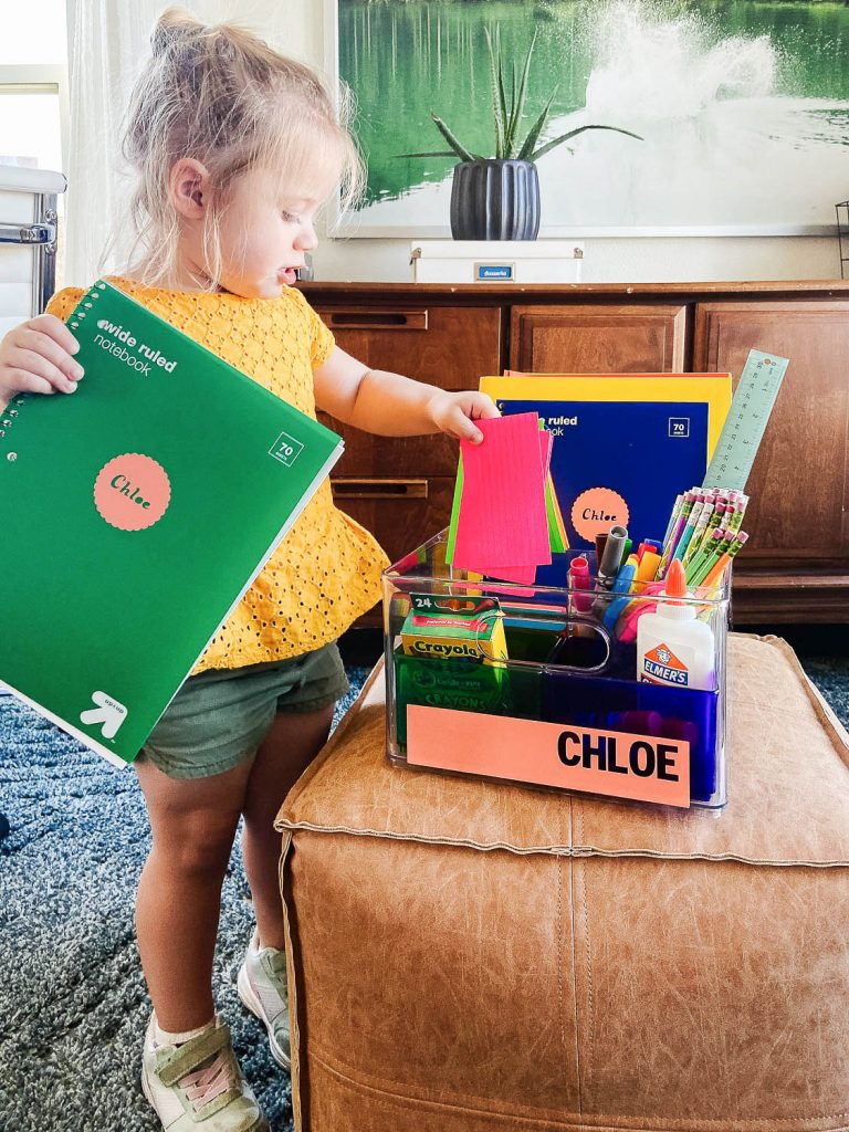 toddler holding notebook and pulling paper out of her homework caddy