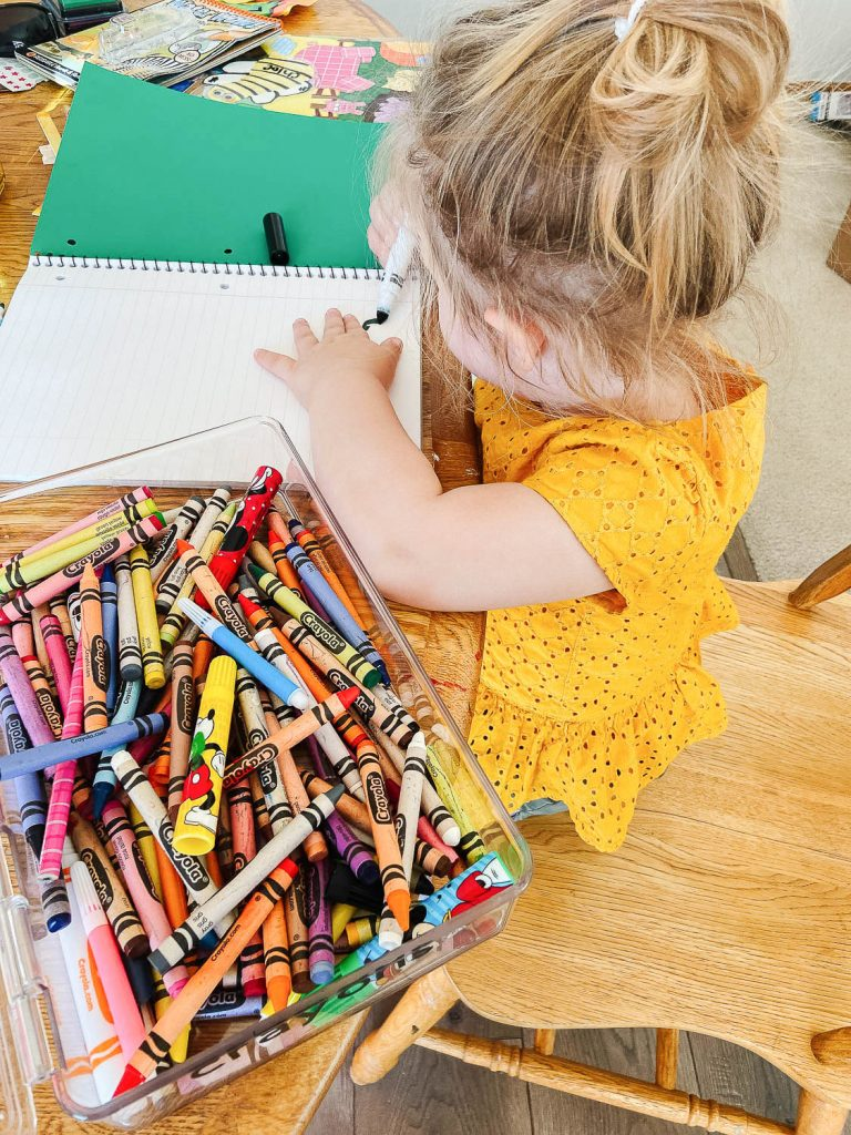 toddler coloring at kitchen table
