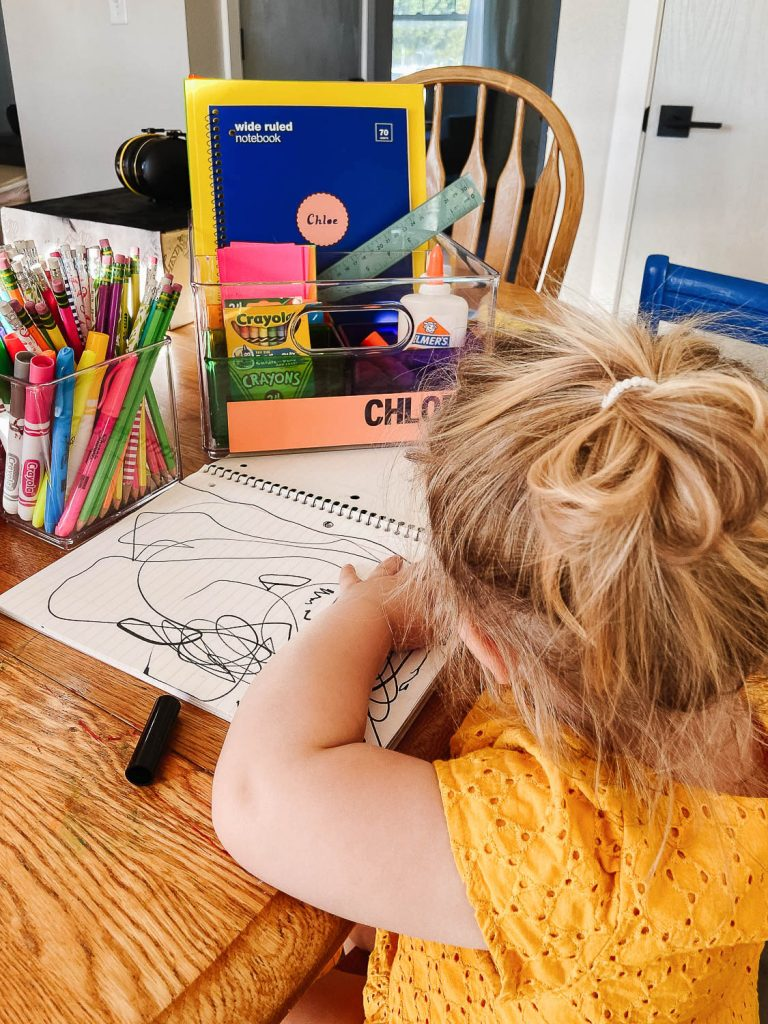 toddler coloring at table with portable homework station in the background