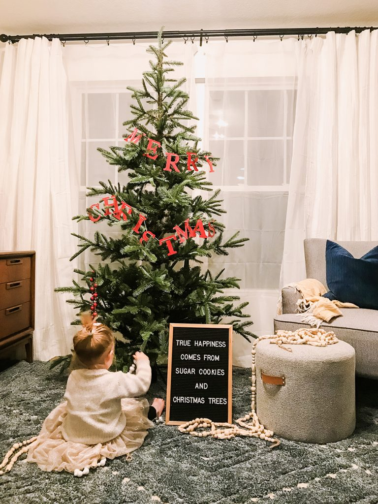 chloe sitting in front of Christmas tree