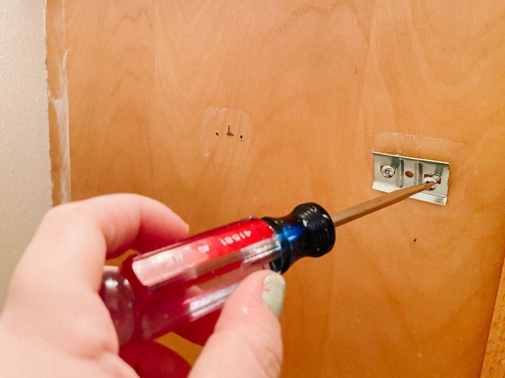screwdriver removing cabinet hardware