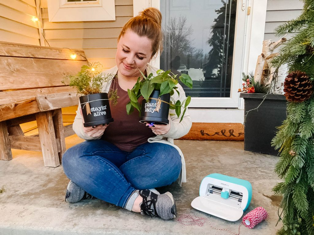 Emily sits on her front porch with two potted plants and her Cricut Joy.