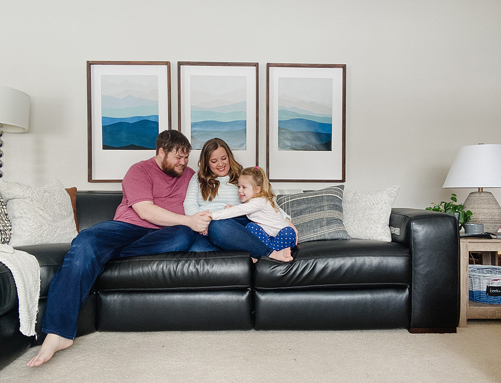family of three sitting on a black leather sofa