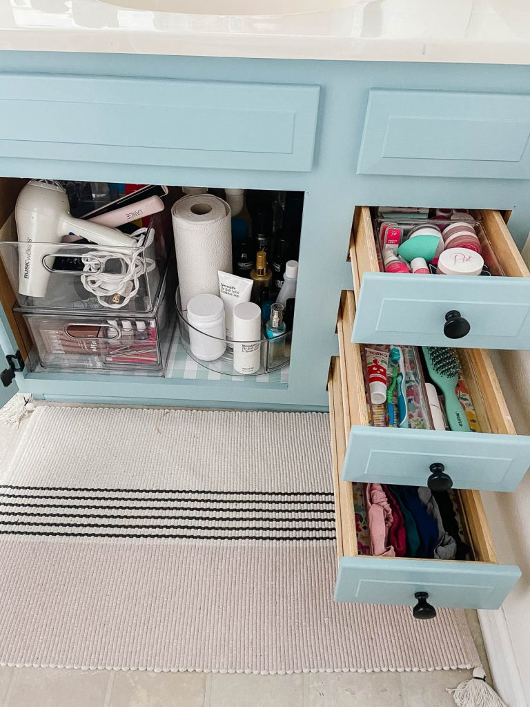 bathroom vanity with drawers and cabinet open and organized