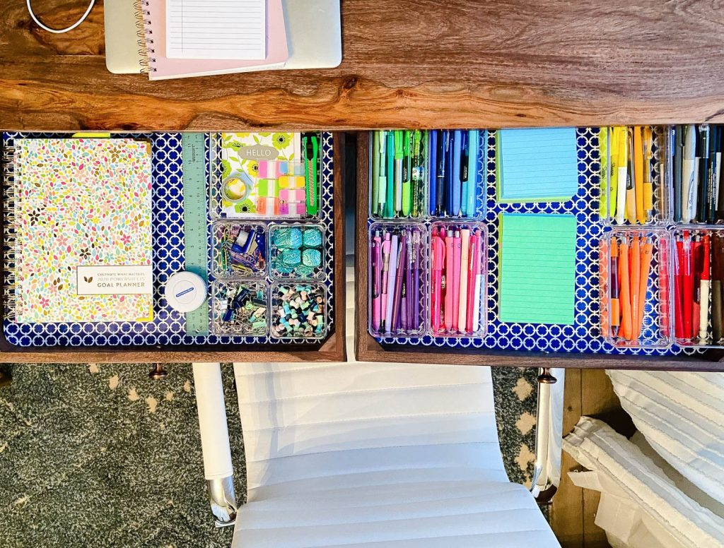 desk drawers with colorful liners and organized supplies
