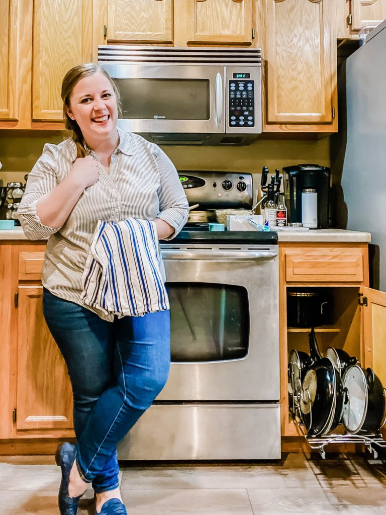 woman in the kitchen with organized cookware cabinet