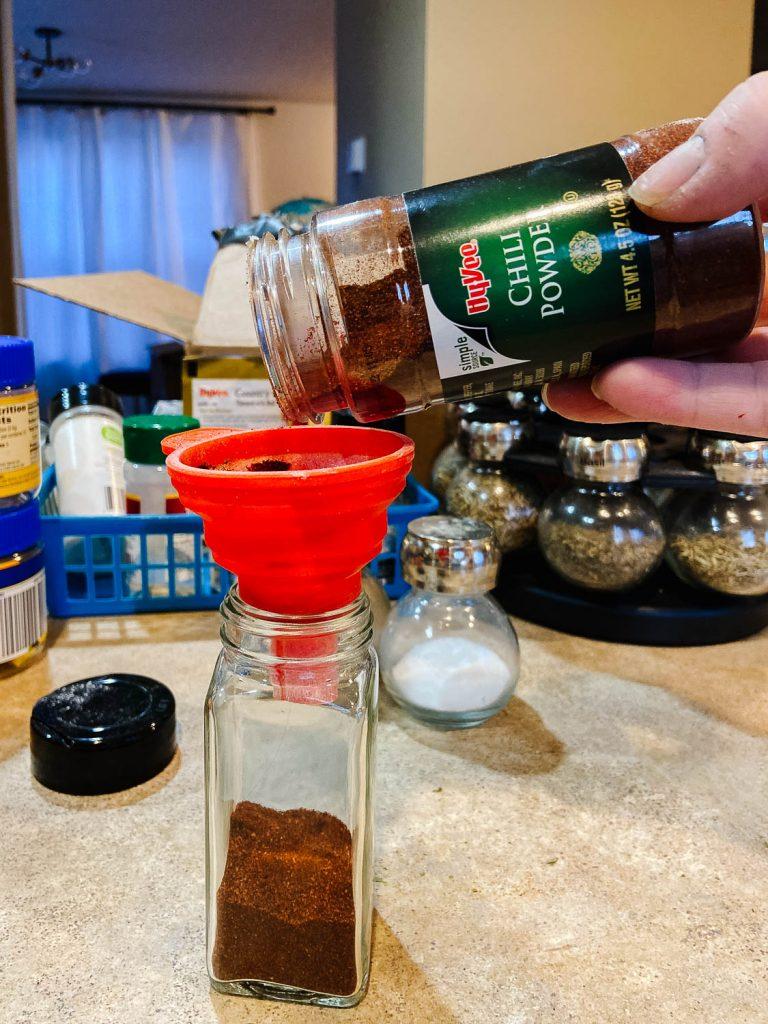 chili powder funneling into a glass jar