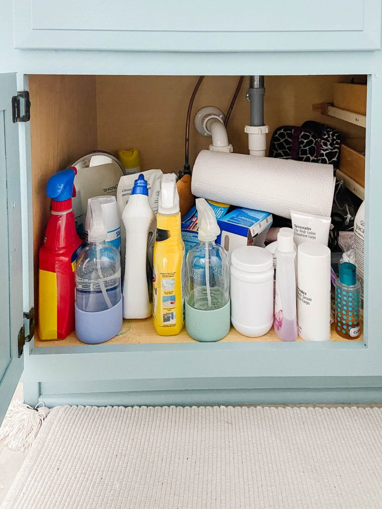 bathroom cabinet full of cleaning and beauty products