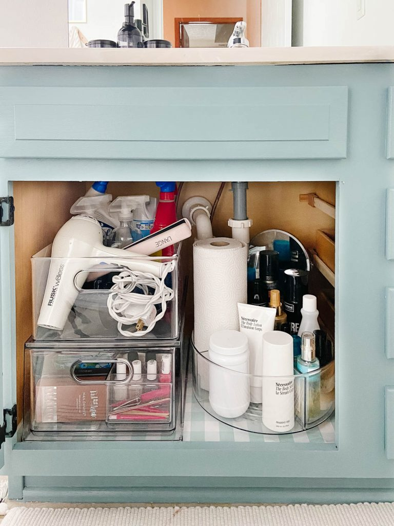 bathroom cabinet with hair and cleaning supplies