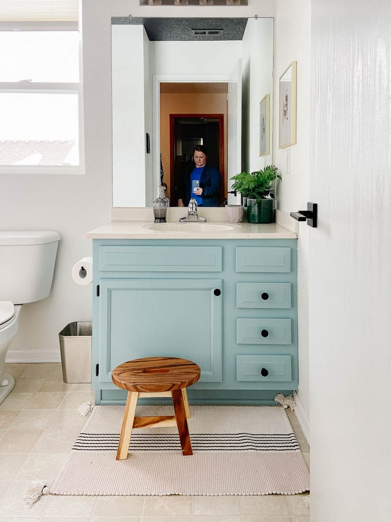 woman taking photo of bathroom vanity in the mirror