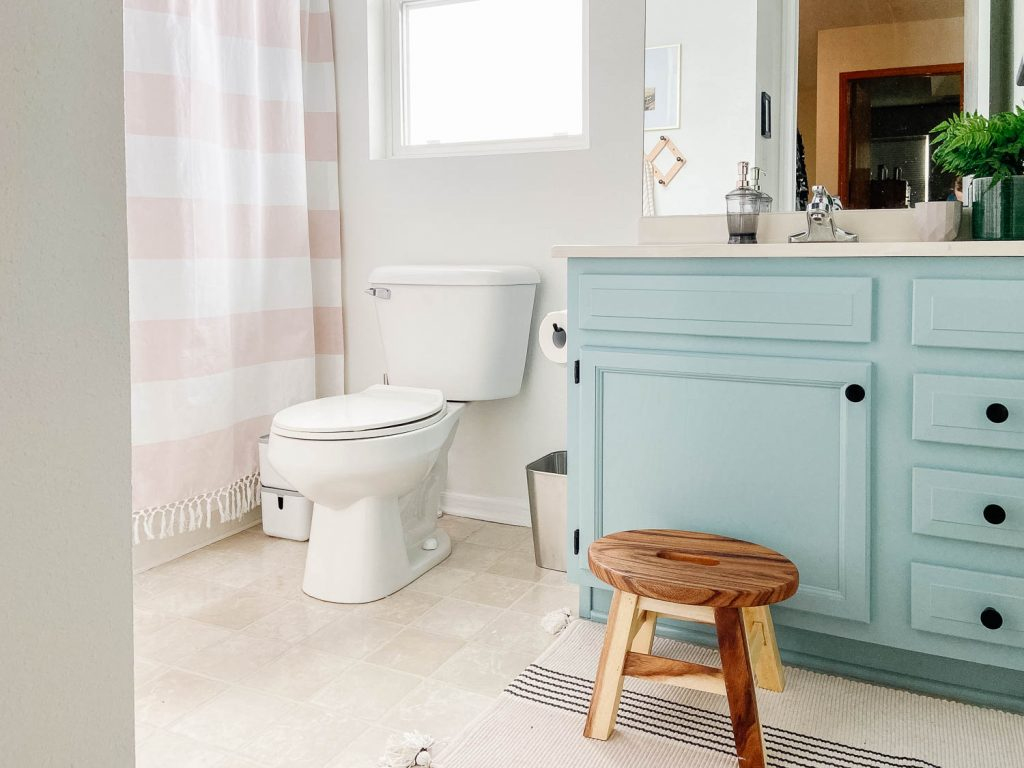 image of bathroom with blue vanity and wood stool