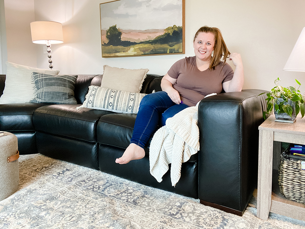 woman sitting on black leather sectional